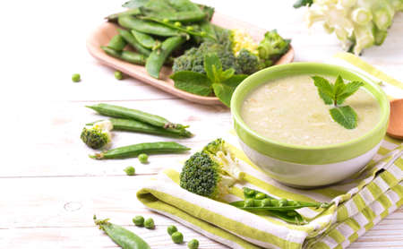 Broccoli and green peas puree soup decorated with mint leafes and almond flakes. Selective focus. Concept of healthy food. Vegetarian. Vegan. Horizontal view. Copyspace Stock Photo