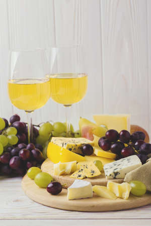 Cheese plate served with honey, fresh grapes and pears on white wooden background. Copyspace. horizontal View