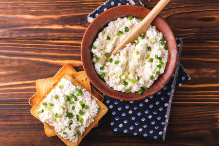 olive green: Clay bowl of goat cream cheese with green onions and olive oil, dip sauce on wooden table, top view Stock Photo
