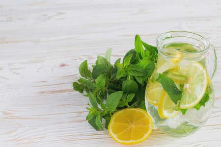 Homemade lemonade with fresh lemon and mint on white wooden background. Stock Photo