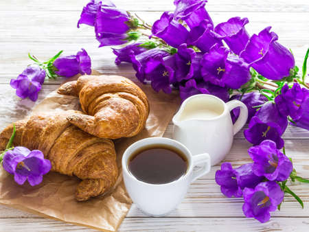 Cup of coffee, milk jar, croissants and bouquet of lilac bellflower flowers on rustic wooden background