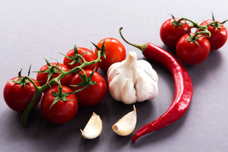 granule: Garlic, hot chili, fresh tomatoes on vine on dark background. ingredients. Top view