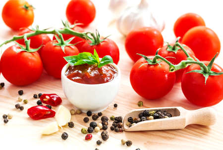 granule: Ketchup. Tomato sauce salsa, hot chili, parsley, fresh tomatoes on vine, garlic, and spices, allspice, on wooden background.