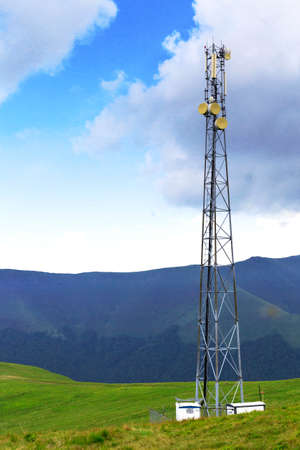 Mobile phone tower silhouette and building with clouds background in Carpathian mountains Stock Photo