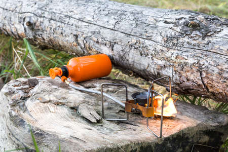 primus: portable gas burner on the wooden logs.
