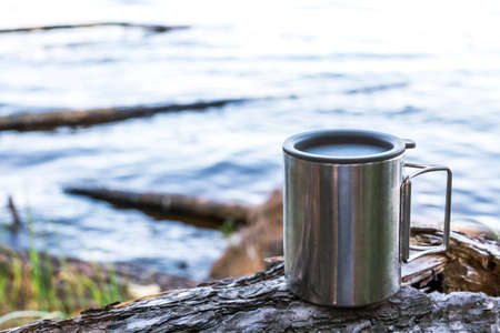 Thermal cup of coffee on wood with nature on background. Tourism and travel