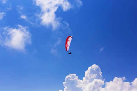 Paraglider flying over clouds in summer day Stock Photo