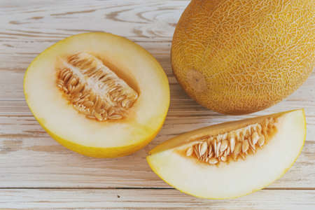 Fresh melons sliced on wooden table