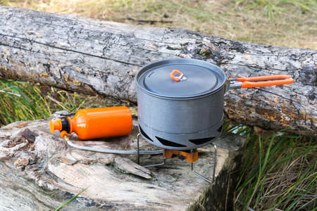 portable gas burner and pot on the wooden logs. Stock Photo - 87513082
