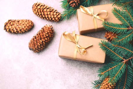 Christmas background. Craft gift boxes and decoration - Christmas tree branches and cones on slate marble background. Flat lay, copy space, top view. Stock Photo