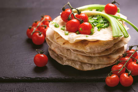 Traditional Kerala Indian cuisine. Homemade flatbread chapati with green onion and cherry tomato on dark slate background. Copyspace, horizontal view, flatlay.