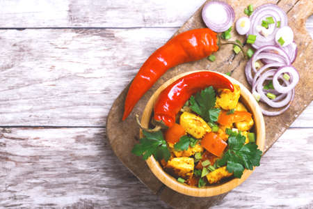 Indian cuisine. Paneer Tikka Kabab with chilli pepper, onions and curry sauce on wooden background. Asian salad. Top view. Copy space