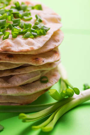 Traditional Kerala Indian cuisine. Homemade flatbread chapati with green onion on green background. Copyspace, horizontal view, flatlay. Color surge trend.