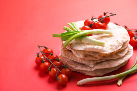 Traditional Kerala Indian cuisine. Homemade flatbread chapati with green onion and cherry tomato on red background. Copyspace, horizontal view, flatlay. Color surge trend.