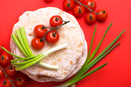 Traditional Kerala Indian cuisine. Homemade flatbread chapati with green onion and cherry tomato on red background. Copyspace, top view, flatlay. Color surge trend.