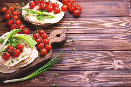 Traditional Kerala Indian cuisine. Homemade flatbread chapati with green onion and cherry tomato on dark wooden background. Copyspace, top view, flatlay.