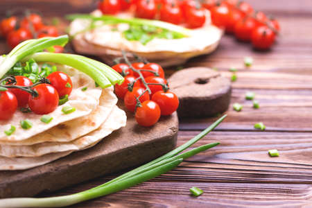 Traditional Kerala Indian cuisine. Homemade flatbread chapati with green onion and cherry tomato on dark wooden background. Copyspace, horizontal view, flatlay.