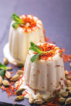 Traditional Rajasthani Indian cuisine. Homemade kulfi dessert, ice cream with safron, mint and nuts on black slate background. Copyspace, horizontal view.