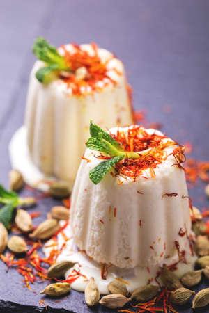 Traditionelle Rajasthani Indische Küche. Selbst gemachter kulfi Nachtisch, Eiscreme mit Safron, Minze und Nüssen auf schwarzem Schieferhintergrund. Exemplar, horizontale Ansicht. Standard-Bild - 94039745