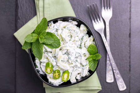 Traditional Indian cuisine. Homemade cucumber raita with yoghurt, garlic, mint, cilantro and spices on black slate background. Greek tzatziki sauce. Copyspace, top view. Stock Photo