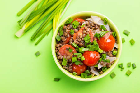 Traditional Indian cuisine. Lentil salad with onion, cherry tomatoes, ginger and lime on green background. Healthy food, vegetarian and vegan snack, clean eating, diet, detox.  Copyspace, top view
