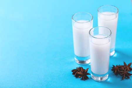 Arabic alcohol drink Raki with anis on blue background.Turkish and Greek Traditional aperitif arak, Ouzo Stock Photo
