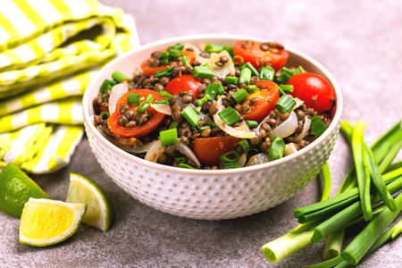 Traditional Indian cuisine. Lentil salad with green onion, cherry tomatoes, ginger and lime on gray slate background. Healthy food, vegetarian and vegan snack, clean eating, diet, detox.  Copyspace, horizontal view