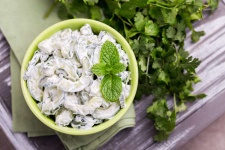 Traditional Indian cuisine. Homemade cucumber raita with yoghurt, garlic, mint, cilantro and spices on wooden background. Greek tzatziki sauce. Copyspace, top view. Stock Photo