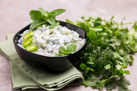Traditional Indian cuisine. Homemade cucumber raita with yoghurt, garlic, mint, cilantro and spices on gray slate background. Greek tzatziki sauce. Copyspace, horizontal view.