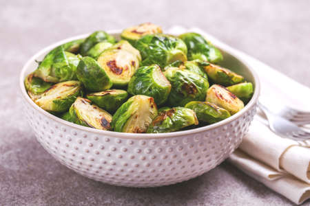Vegetarian cuisine. Homemade Brussels Sprouts roasted with olive oil on gray slate background. Copyspace, horizontal view, flatlay. Standard-Bild
