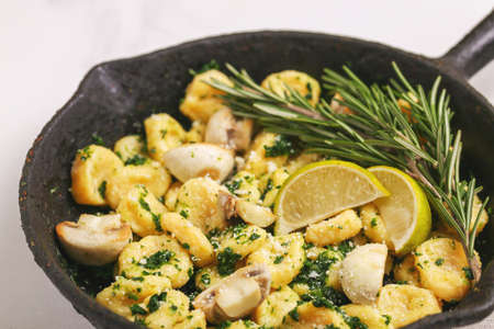 Traditional Italian cuisine. Gnocchi with a cream sauce, olives and rosemary on white background. Copyspace, top view