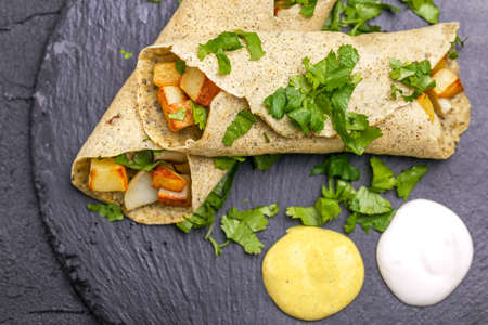 Traditional Indian cuisine. Vegetarian masala dosa with fried potato filling and chutney and sambar sauces. Copyspace, top view, flatlay