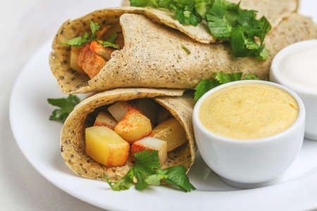 Traditional Indian cuisine. Vegetarian masala dosa with fried potato filling and chutney and sambar sauces. Copyspace, horizontal view, flatlay