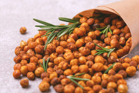 Traditional Indian cuisine. Roasted spicy chickpeas with lime and rosemary on gray slate background. Copyspace, horizontal view.