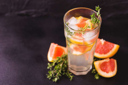 Alcoholic cocktail gin bitter lemon with thyme and grapefruit. Fruit lemonade. Black background. Horizontal view. Copy space Stock Photo
