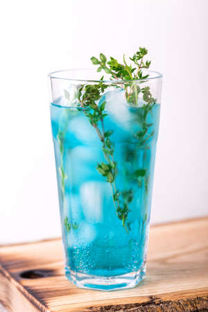 Ice Blue cocktail with thyme. Blue curacao liqueur. Summer drink Stock Photo