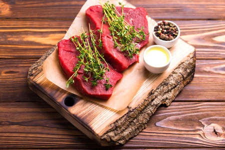Fresh raw beef tenderloin and marbled steaks on wooden cutting board with seasoning. Top view. Stock Photo