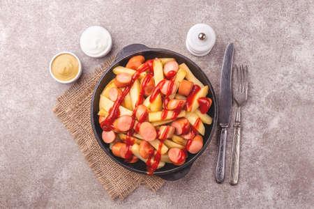 Frites de salchipapa péruviennes traditionnelles faites maison avec mayonnaise, ketchup et sauces à la moutarde. Frites avec des saucisses. Fast food