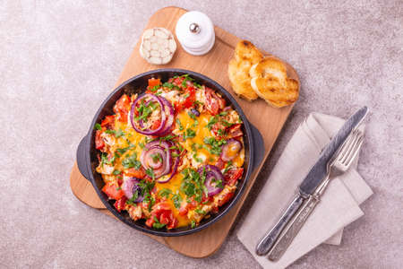 Shakshuka with bread toasts in a pan. Middle eastern and jewish traditional cuisine. Fried eggs with tomatoes, bell pepper, garlic, onion, vegetables and herbs.