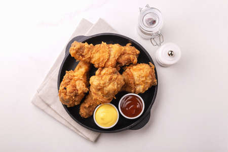 Fried crispy and spicy chicken legs with sauces. Fast and junk food concept. Top view, copyspace Stockfoto