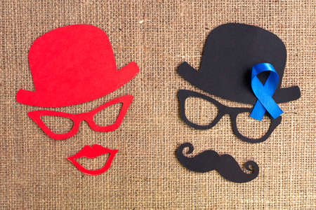 Male and female silhouette patterns with blue ribbon symbol on the burlap background. November concept. Prostate Cancer and men's health awareness. Funny party faces
