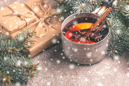 Hot mulled wine in a small vintage pan with christmas tree on the gray slate background with snowy effect. Christmas or winter warming drink. Horizontal view. Copy space Imagens