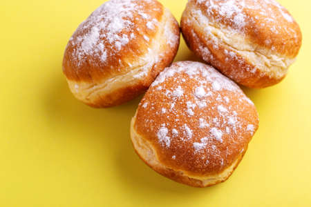 Tasty sweet donuts with powdered sugar on bright yellow background. Traditional Jewish sweet Hanukkah dish