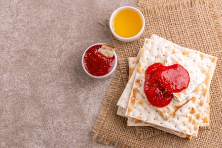 Traditional Jewish kosher matzo with jam and honey on rustic burlap napkin. Copy space