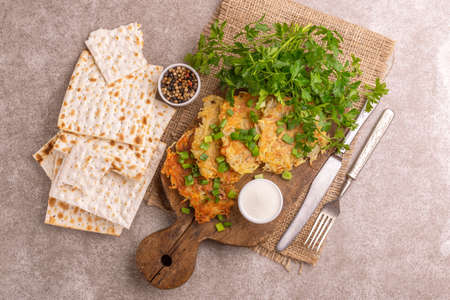 Homemade traditional potato pancakes Hanukkah celebration food with crunchy matzo on vintage cutting board. Gray marble background