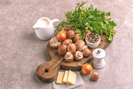 Fresh ingredients for tasty pureed mushroom soup. Healthy food concept. Gray marble background. Horizontal view. Copy space