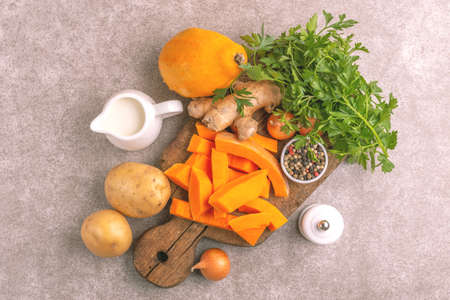 Fresh ingredients for tasty pureed pumpkin soup. Healthy food concept. Gray marble background. Top view. Copy space