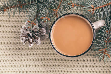 White cup of hot cocoa and christmas tree with cones. Knitted plaid background. Top view. Close up Foto de archivo