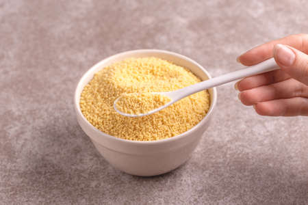 Full spoon of raw couscous grain in clay bowl on gray marble background. Copy space. Horizontal view