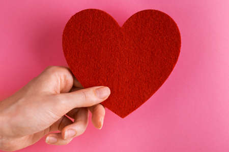 Red felt heart in woman's hand on bright pink background. Copy space 版權商用圖片